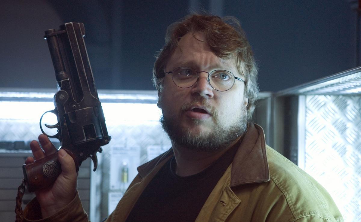 Guillermo del Toro mit Hellboys Waffe, beim Dreh zu 'Hellboy 2 - Die goldene Armee' (USA/Deutschland 2008) © Universal Pictures